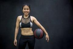 Mujer asiática joven en el sportwear que lleva a cabo baloncesto Foto de archivo libre de regalías