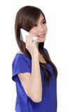 Mujer asiática joven en el teléfono que sonríe, aislada en blanco Fotografía de archivo