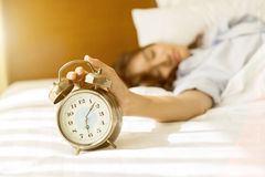 Mujer asiática joven en la cama que intenta despertar con el despertador Fotos de archivo libres de regalías