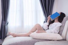 Mujer asiática joven en la camisa blanca que duerme en cama Fotografía de archivo libre de regalías
