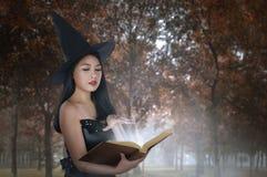 Mujer asiática joven en libro del encanto de la tenencia del traje de las brujas Fotos de archivo libres de regalías