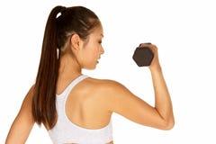 Mujer asiática joven en sujetador de los deportes con pesa de gimnasia Foto de archivo libre de regalías