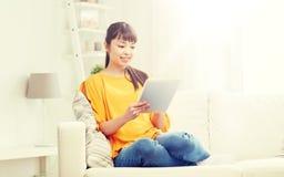 Mujer asiática joven feliz con PC de la tableta en casa Fotos de archivo