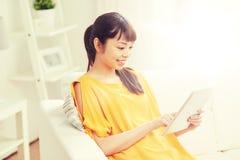 Mujer asiática joven feliz con PC de la tableta en casa Foto de archivo libre de regalías