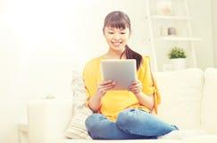 Mujer asiática joven feliz con PC de la tableta en casa Imágenes de archivo libres de regalías