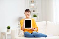 Mujer asiática joven feliz con PC de la tableta en casa Foto de archivo