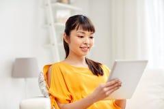 Mujer asiática joven feliz con PC de la tableta en casa Fotos de archivo libres de regalías