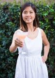 Mujer asiática joven feliz hermosa que goza de un martini Foto de archivo