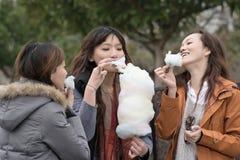 Mujer asiática joven feliz que come el caramelo de algodón con sus amigos imagenes de archivo