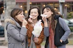 Mujer asiática joven feliz que come el caramelo de algodón con sus amigos foto de archivo libre de regalías