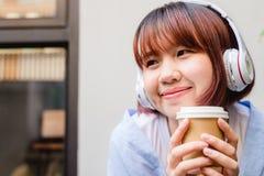 Mujer asiática joven feliz que escucha la música en una cafetería que sostiene una taza de café en su mano Fotografía de archivo