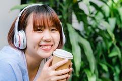 Mujer asiática joven feliz que escucha la música en una cafetería que sostiene una taza de café en su mano Imágenes de archivo libres de regalías