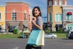 Mujer asiática joven feliz que hace compras un mercado al aire libre Fotos de archivo libres de regalías