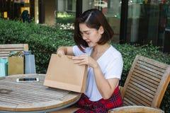 Mujer asiática joven feliz que hace compras un mercado al aire libre con el fondo de edificios en colores pastel y del cielo azul Fotografía de archivo