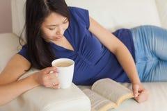Mujer asiática joven feliz que miente en el sofá que lee una tenencia del libro foto de archivo