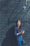 Mujer asiática joven feliz que usa el smartphone al aire libre en soleado brillante Foto de archivo libre de regalías