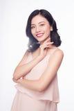Mujer asiática joven feliz que usa el smartphone que se coloca sobre azul Imágenes de archivo libres de regalías