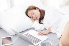 Mujer asiática joven hermosa con el ordenador portátil que se acuesta en dormitorio Foto de archivo libre de regalías