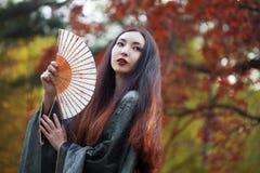 Mujer asiática joven hermosa con la fan en fondo del arce rojo Foto de archivo