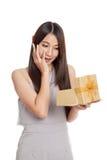 Mujer asiática joven hermosa emocionada con la caja de regalo de oro Foto de archivo