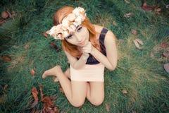 Mujer asiática joven hermosa en el prado verde con las hojas marrones Imagen de archivo
