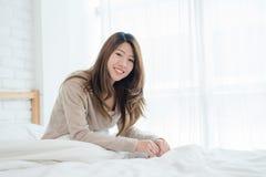 Mujer asiática joven hermosa feliz que despierta por mañana, sentándose en la cama, estirando en dormitorio acogedor Fotos de archivo
