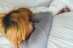 Mujer asiática joven hermosa que duerme en cama por la mañana Hora de acostarse asiática atractiva del uso de la muchacha en su d Imagen de archivo