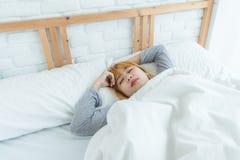 Mujer asiática joven hermosa que duerme en cama por la mañana Hora de acostarse asiática atractiva del uso de la muchacha en su d Imagenes de archivo