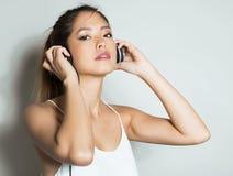 Mujer asiática joven hermosa que escucha la música con los auriculares Fotografía de archivo libre de regalías