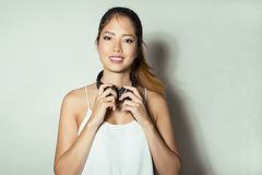 Mujer asiática joven hermosa que escucha la música con los auriculares Imagenes de archivo