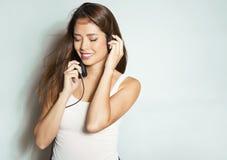 Mujer asiática joven hermosa que escucha la música con los auriculares Imagen de archivo