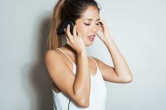 Mujer asiática joven hermosa que escucha la música con los auriculares Fotografía de archivo