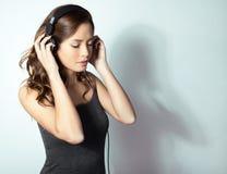 Mujer asiática joven hermosa que escucha la música con los auriculares Fotos de archivo