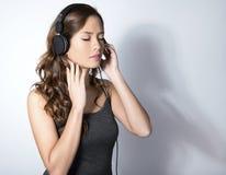Mujer asiática joven hermosa que escucha la música con los auriculares Fotos de archivo libres de regalías