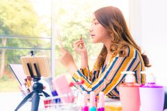 Mujer asiática joven hermosa que hace estudio en línea del producto en casa fotografía de archivo