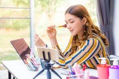 Mujer asiática joven hermosa que hace estudio en línea del producto en casa imagenes de archivo
