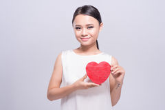 Mujer asiática joven hermosa que lleva a cabo el corazón rojo en blanco Fotos de archivo libres de regalías