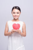 Mujer asiática joven hermosa que lleva a cabo el corazón rojo en blanco Fotografía de archivo