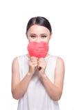 Mujer asiática joven hermosa que lleva a cabo el corazón rojo en blanco Imagenes de archivo