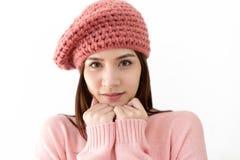 Mujer asiática joven hermosa que lleva frío hecho punto del rosa del suéter y que guarda las manos en la barbilla que mira la cám imagenes de archivo