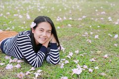 Mujer asiática joven hermosa que miente en campo verde con completamente la flor del rosa de la caída en el jardín al aire libre foto de archivo libre de regalías