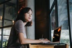 Mujer asiática joven hermosa que trabaja en una cafetería con un ordenador portátil fotografía de archivo