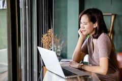 Mujer asiática joven hermosa que trabaja en una cafetería con un ordenador portátil imagen de archivo