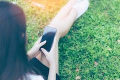 Mujer asiática joven hermosa que usa smartphone en jardín Fotografía de archivo