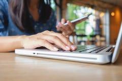 Mujer asiática joven hermosa que usa smartphone y sosteniendo la tarjeta para el pago en línea que hace compras Concepto de las c Foto de archivo libre de regalías