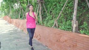 Mujer asiática joven hermosa sana del corredor en la ropa de los deportes que corre y que activa en la calle en parque urbano de  metrajes