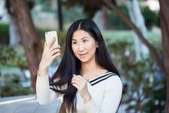 Mujer asiática joven linda en un parque hermoso usando su teléfono Foto de archivo