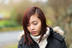 Mujer asiática joven pensativa que se coloca al aire libre Fotos de archivo libres de regalías