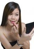 Mujer asiática joven que aplica maquillaje Fotografía de archivo libre de regalías