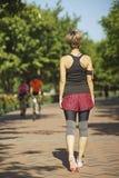 Mujer asiática joven que camina en parque de la ciudad después de activar Foto de archivo